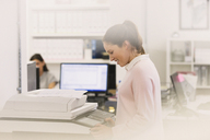 Smiling businesswoman making copies at copier in office - HOXF00930