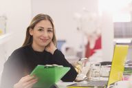 Portrait smiling fashion buyer with clipboard working at laptop in office - HOXF00933