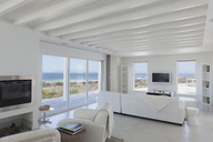 Beach house living room with wood beam ceilings - HOXF00957