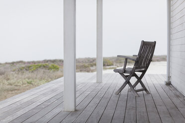 Wooden folding chair on beach house deck - HOXF00984