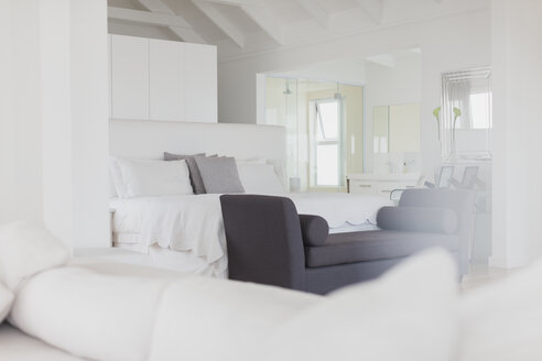 White bedroom with en suite bathroom in home showcase interior - HOXF00990