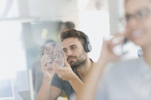 Businessman with headphones examining prototype - HOXF00999