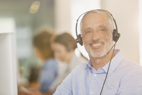 Portrait smiling businessman with headset in office - HOXF01005