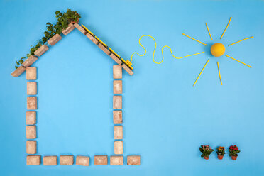 House shape made of bricks on blue background, with solar panels plugged to sun - BAEF01540
