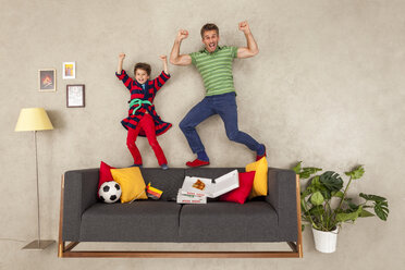 Father and son watching football in living room - BAEF01543