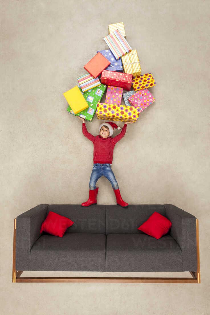 Boy with Santa hat holding pile of Christmas presents - BAEF01573 - Leander Baerenz/Westend61