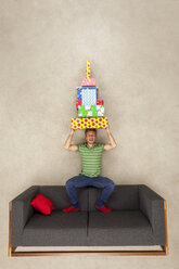 Man sitting on couch, balancing pile of presents on his head - BAEF01576