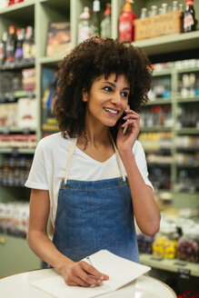 Smiling woman on the phone in a store taking notes - EBSF02193