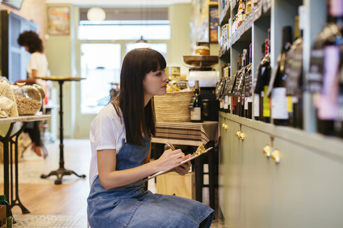 Woman with clipboard at shelf in a store - EBSF02223