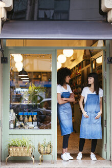 Two smiling women standing in entrance door of a store - EBSF02229