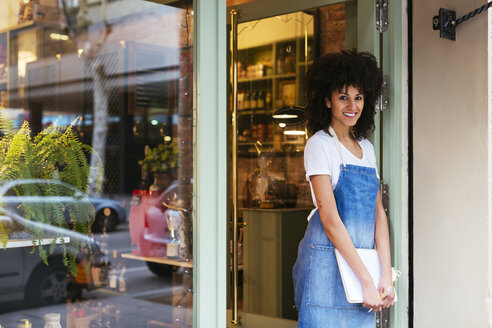 Portrait of smiling woman standing in entrance door of a store - EBSF02235