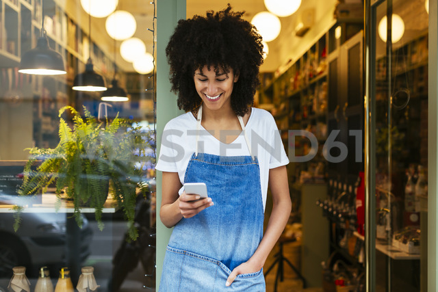 Smiling woman using cell phone in entrance door of a store - EBSF02238 - Bonninstudio/Westend61