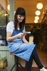 Smiling woman sitting on stool using cell phone at entrance door of a store - EBSF02241