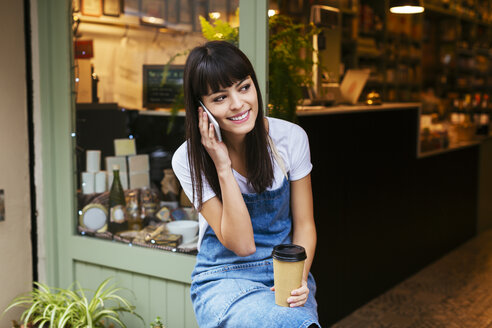 Smiling woman sitting at entrance door of a store talking on cell phone - EBSF02244