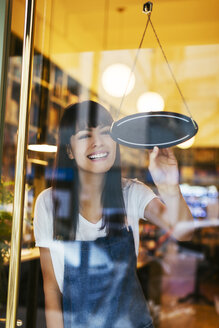 Happy woman turning sign in window of a store - EBSF02247