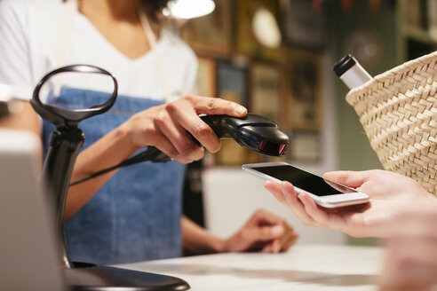 Close-up of customer paying cashless with smartphone at counter of a store - EBSF02259