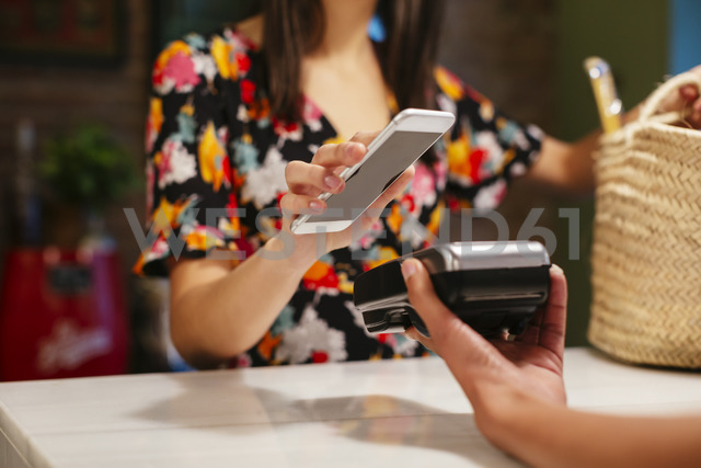 Close-up of customer paying cashless with smartphone at counter of a store - EBSF02262 - Bonninstudio/Westend61