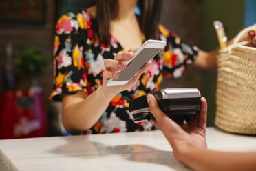 Close-up of customer paying cashless with smartphone at counter of a store - EBSF02262