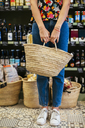 Low section of customer holding basket in a store - EBSF02265