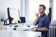 Smiling man using smartphone at desk in office - BSZF00238