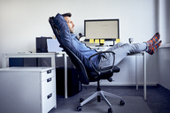 Man sitting at desk in office relaxing - BSZF00250