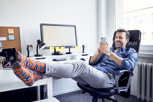 Relaxed man sitting at desk in office using cell phone - BSZF00253