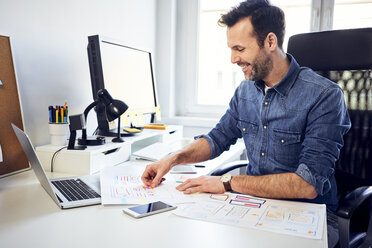 Smiling web designer working on draft at desk in office - BSZF00262