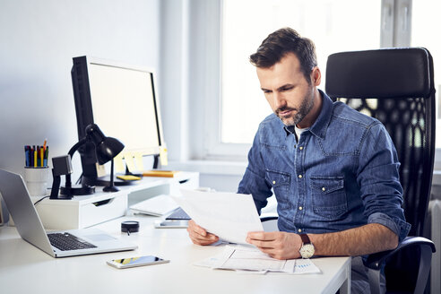 Man reading document at desk in office - BSZF00265