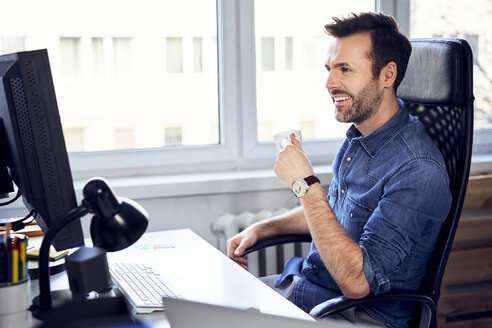Smiling man looking at computer and drinking coffee at desk in office - BSZF00268