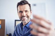 Happy man in office taking selfie - BSZF00274