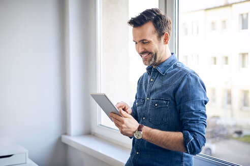 Smiling man using tablet at the window - BSZF00277