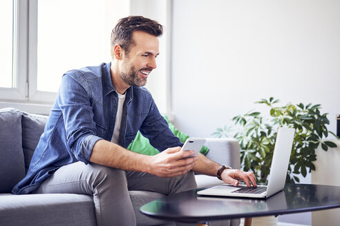 Smiling man sitting on sofa using laptop and cell phone - BSZF00280