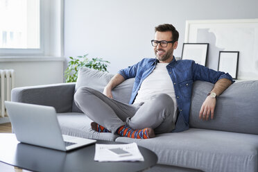Relaxed smiling man sitting on sofa looking at laptop - BSZF00286