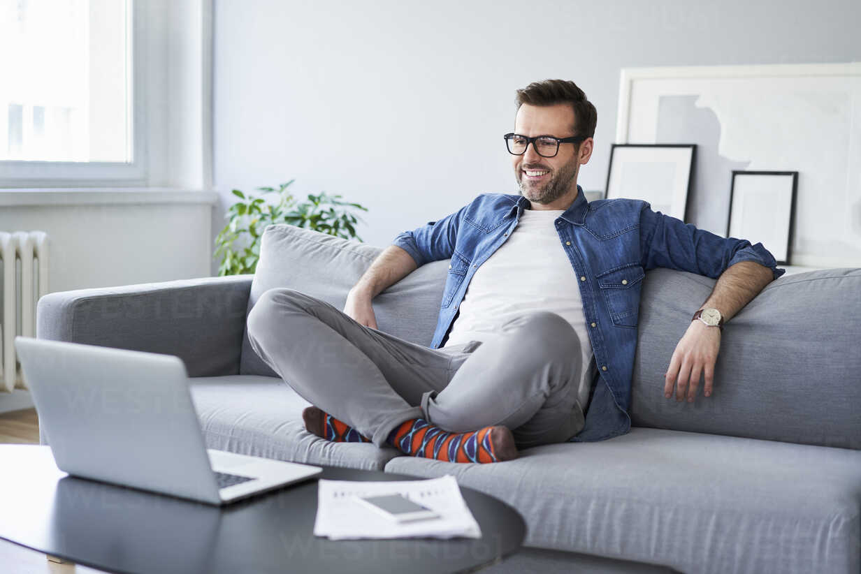 Relaxed smiling man sitting on sofa looking at laptop - BSZF00286 - Bartek Szewczyk/Westend61