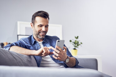 Smiling man sitting on sofa using cell phone - BSZF00292