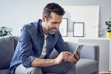 Smiling man sitting on sofa using cell phone - BSZF00295
