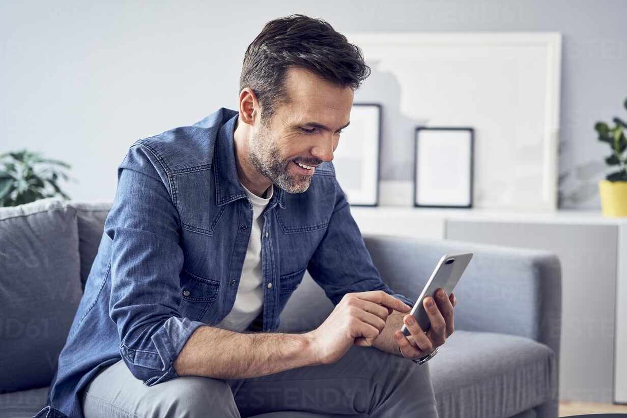 Smiling man sitting on sofa using cell phone - BSZF00295 - Bartek Szewczyk/Westend61