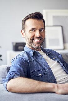 Portrait of smiling man sitting on sofa - BSZF00298