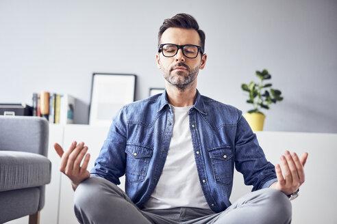 Relaxed man meditating at home - BSZF00304
