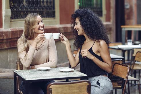Two happy friends drinking coffee in sidewalk cafe - JSMF00049