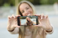 Happy young woman taking selfie with cell phone, close-up - JSMF00055