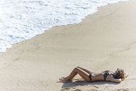 Indonesia, Bali, young woman lying at the beach - KNTF01056
