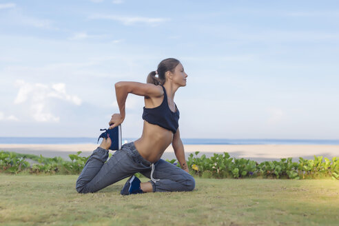 Indonesia, Bali, woman stretching - KNTF01059