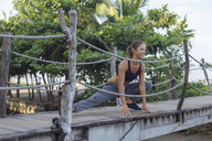 Indonesia, Bali, woman stretching - KNTF01074