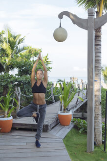 Indonesia, Bali, woman practicing yoga, tree position - KNTF01080