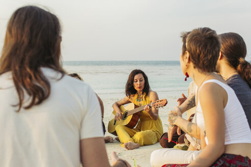 Thailand, Koh Phangan, group of people sitting on a beach with guitar - MOMF00382