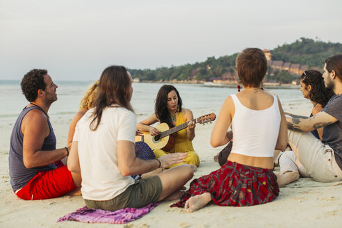 Thailand, Koh Phangan, group of people sitting on a beach with guitar - MOMF00385