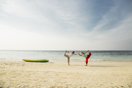 Thailand, Koh Phangan, couple doing yoga on a beach - MOMF00388
