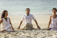 Thailand, Koh Phangan, three people doing yoga on a beach - MOMF00391