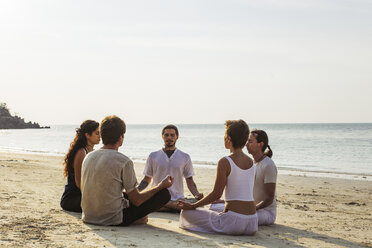 Thailand, Koh Phangan, group of people meditating together on a beach - MOMF00394
